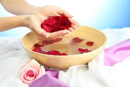 woman hands with wooden bowl of water with petals, on blue background Stock Photo - 16219867