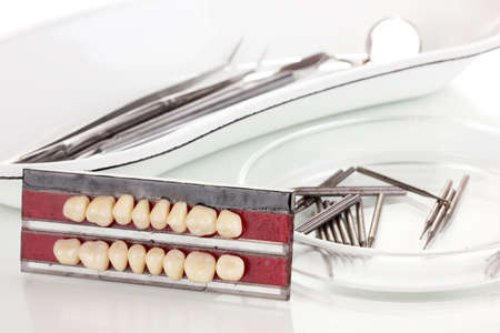 denture with dental tools isolated on white photo