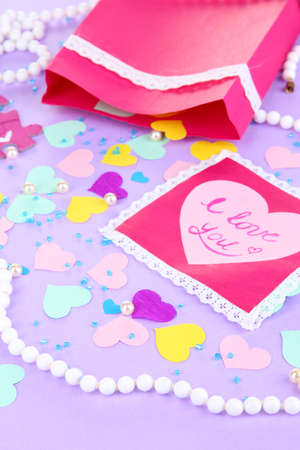 a frill: Beautiful composition of paper valentines and decorations on purple background close-up