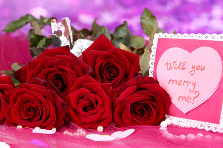 reciprocity: Beautiful bouquet of roses with valentine on pink fabric on purple background close-up
