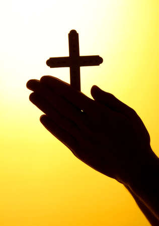 cross arms: man hands with crucifix, on yellow background