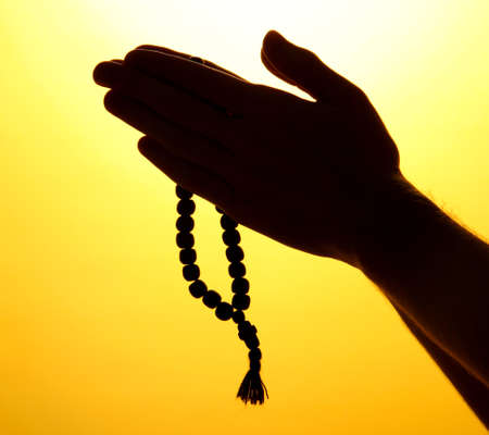 male hands with rosary, on yellow background Stock Photo - 16218367