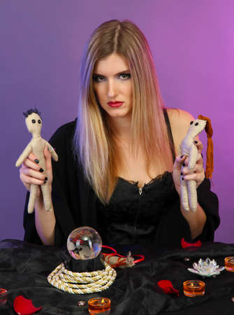 Witch with voodoo dolls on color background photo