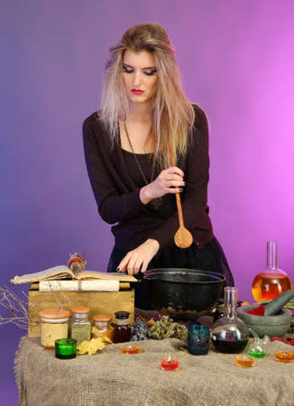 Halloween witch stirring in poison soup in her cauldron on color background photo
