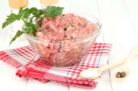 Bowl of raw ground meat with spices on wooden table Stock Photo