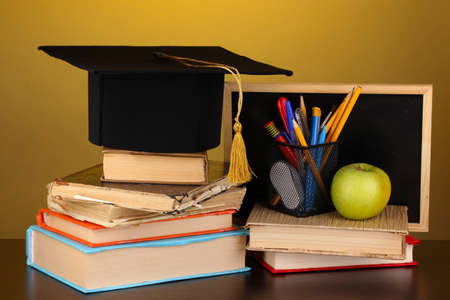 Books and magister cap against school board on wooden table on yellow background photo