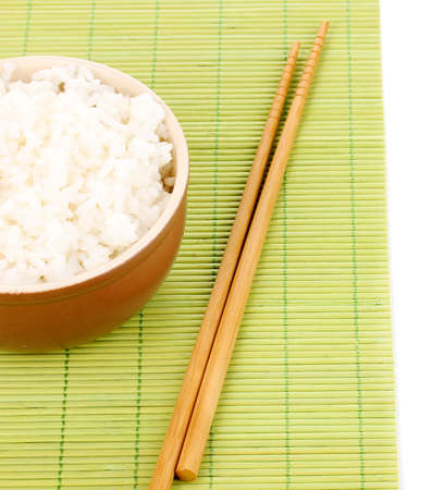 Bowl of rice and chopsticks on bamboo mat isolated on white photo