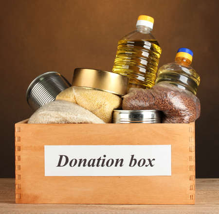 Donation box with food on brown background close-up photo