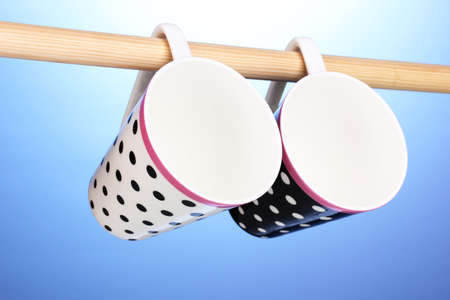 Nice cups hanging on stick on blue background photo