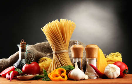 cooking oil: Pasta spaghetti, vegetables and spices, on wooden table, on grey background