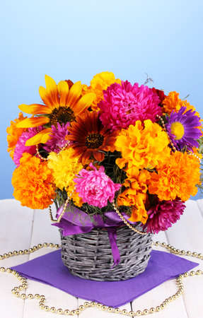 ronantic: Beautiful bouquet of bright flowers on wooden table on blue background