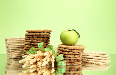 tasty crispbread, apple, measuring tape and ears, on green background Stock Photo - 16276303