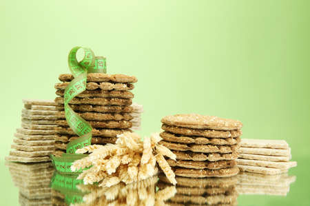 galettes: tasty crispbread, ears and measuring tape, on green background Stock Photo