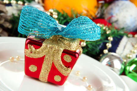 Small Christmas gift on plate on serving Christmas table background close-up Stock Photo - 16275425