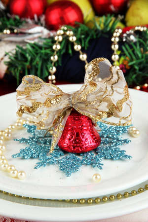 Small Christmas bell on a plate on serving Christmas table background close-up photo
