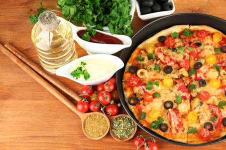 colorful composition of delicious pizza, vegetables and spices on wooden background close-up Stock Photo - 16311249