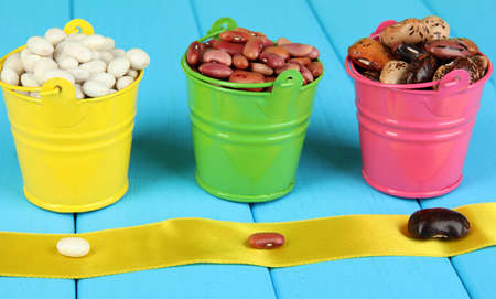 Different types of beans in colored buckets close-up on blue wooden table Stock Photo - 16317183