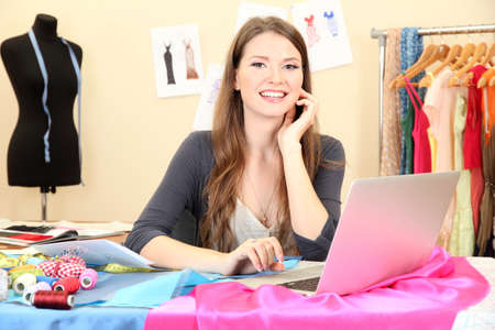 business costume: beautiful young dressmaker in workroom Stock Photo