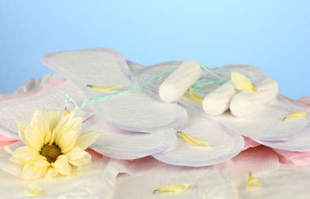 various types of sanitary pads and tampons on blue background close-up photo