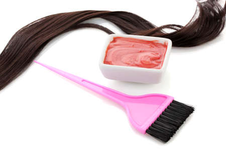 strand of hair: Bowl with hair dye and pink brush on white background close-up