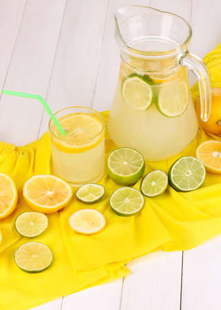 Citrus lemonade in glass and pitcher of citrus around on yellow fabric on white wooden table close-up Stock Photo - 16318639