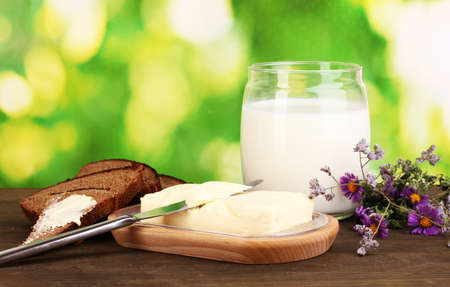 Butter on wooden holder surrounded by bread and milk on wooden table on natural background close-up Stock Photo - 16317277