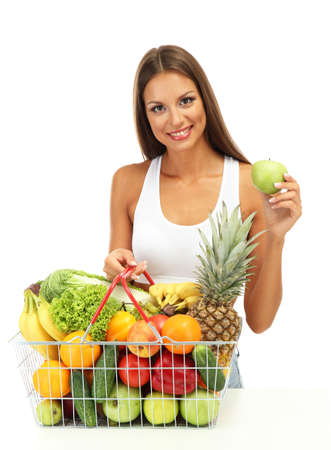 beautiful young woman with fruits and vegetables in shopping basket, isolated on white photo