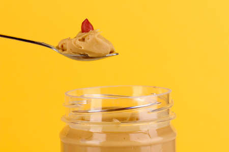Delicious peanut butter in jar and spoon on yellow background photo