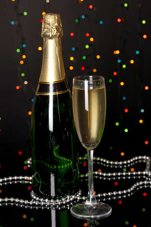 Celebratory champagne with wineglass on Christmas lights background photo