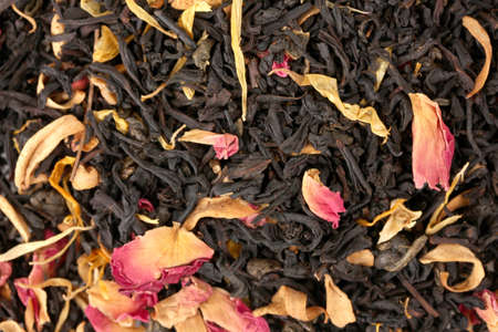 aromatic black dry tea with fruits and petals, close up photo