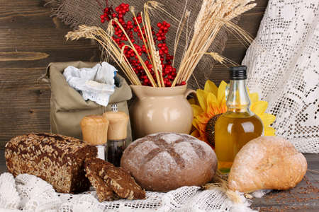 Different types of rye bread on wooden table on autumn composition background photo