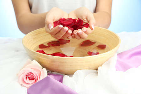 woman hands with wooden bowl of water with petals, on blue background Stock Photo - 16313904