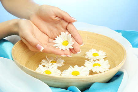 heal care: woman hands with wooden bowl of water with flowers, on blue background Stock Photo