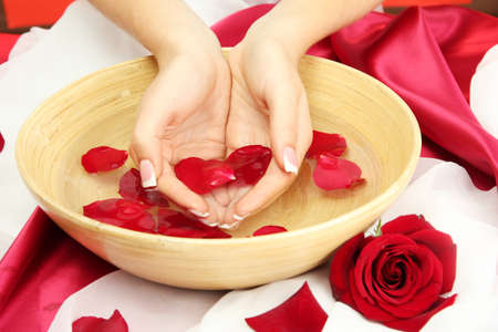 woman hands with wooden bowl of water with petals, on red background Stock Photo - 16318634