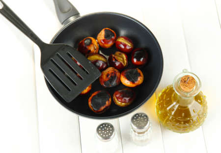 decanter: roasted chestnuts in the pan and decanter with oil, salt and pepper on white wooden background