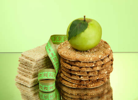 tasty crispbread, apple and measuring tape, on green background photo