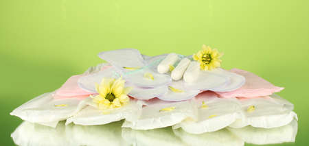 various types of sanitary pads and tampons on green background close-up photo