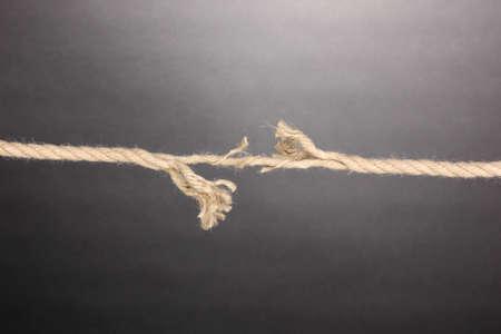 resistencia: Romper la cuerda sobre fondo gris Foto de archivo
