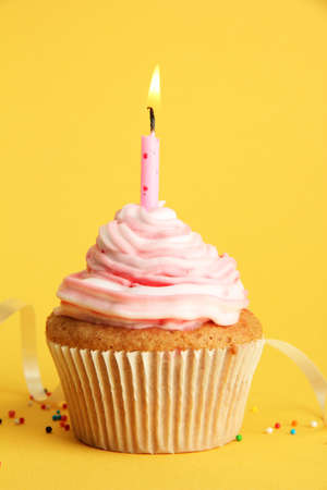 tasty birthday cupcake with candle, on yellow background photo