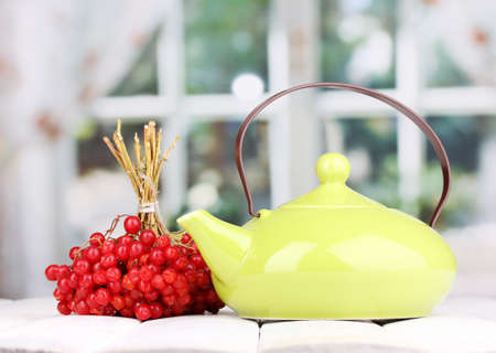 tea with red viburnum on table on bright background photo