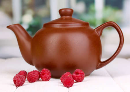 tea with raspberries on table on bright background photo