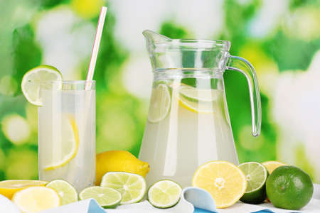 Citrus lemonade in pitcher and glass of citrus around on natural wooden table on blue background photo