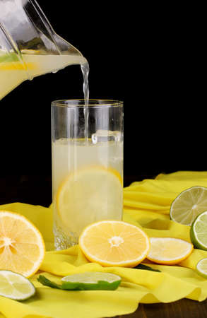 Citrus lemonade in glass and pitcher of citrus around on yellow fabric on wooden table close-up Stock Photo - 16344441