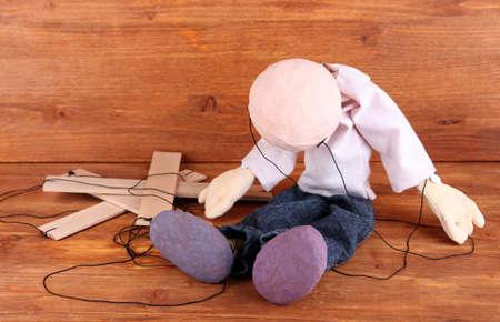 marioneta de madera: Marioneta de madera que se sienta en el fondo de madera Foto de archivo