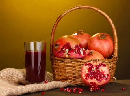 Ripe pomegranates on basket with glass of pomegranate juice on wooden table on yellow background photo