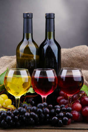 bottles and glasses of wine and grapes on grey background photo
