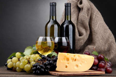 bottles and glasses of wine, cheese and grapes on grey background Stock Photo - 16343849
