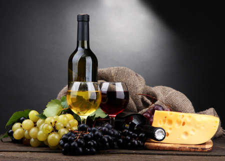 bottles and glasses of wine, cheese and grapes on grey background photo