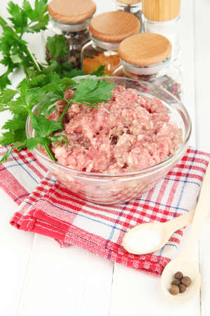 Bowl of raw ground meat with spices on wooden table Stock Photo - 16343653