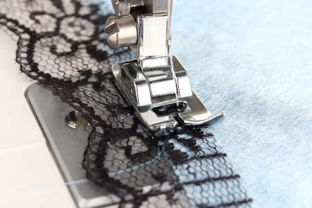 Closeup of sewing machine working part with  blue cloth photo